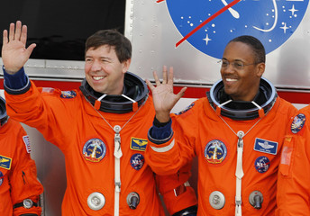 Space shuttle Discovery crew members Mission Specialist Michael Barratt and Benjamin Drew Jr. wave as they depart their quarters at the Kennedy Space Center