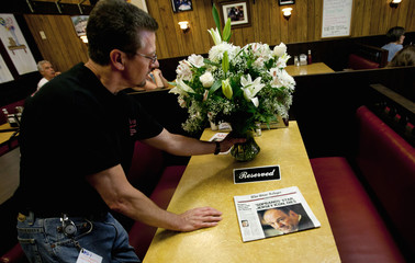 "Ron Stark, owner of Holsten's Ice Cream Shop adjusts bouquet of flowers on booth in his restaurant, the set for final scene in ""The Sopranos"", in Bloomfield"