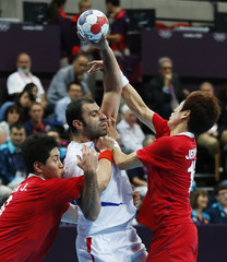 Serbia's Ivan Stankovic is challenged by South Korea's Park Junggeu and Jeong Han in their men's handball Preliminaries Group B match at the Copper Box venue during the London 2012 Olympic Games