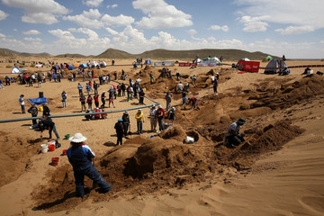 """Artists work on sand sculptures that depicts the Bible stories during Holy Week celebrations in """"Arenal de Cochiraya"""", on the outskirts of Oruro"""