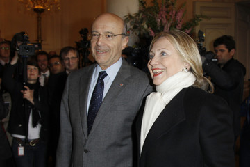 """US Secretary of State Clinton is greeted by French Foreign Minister Juppe on arrival to attend a meeting, """"The Friends of Syria"""" in Paris"""