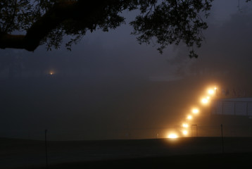 Masters grounds crews use the headlights on their mowers as they prepare the course in the early morning hours before the final round of the Masters golf tournament at the Augusta National Golf Course in Augusta