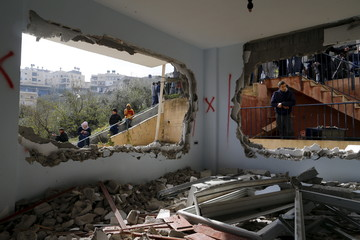 Relatives and onlookers look at the demolished house of Palestinian Allyan in Jabel Mukaber