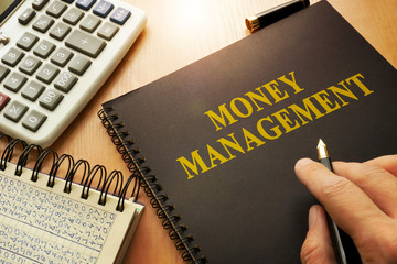 Book with money management on a table.