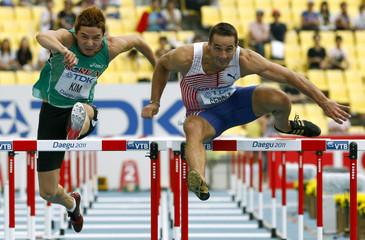 Roman Sebrle of the Czech Republic clears a hurdle next to Kun-Woo Kim of South Korea during their 110 metres hurdles heat in Daegu