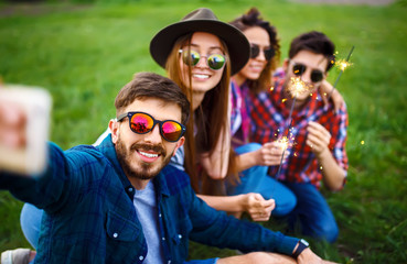 Group of friends enjoying party.people are making selfies. people with christmas sparklers.Everyone has a great mood. Summer time.