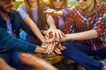 young people putting their hands together. Friends with stack of hands showing unity and teamwork.Group of friends enjoying party. Everyone has a great mood. Summer time.