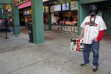 A baseball fan wearing a Darth Vader mask from the Star Wars movies waits under the stands at Fenway Park in Boston