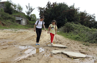 Marie Gjana, and her sister Fatbardha walk home from school to their Communist-era heavy cannon bunker home, just outside the capital Tirana