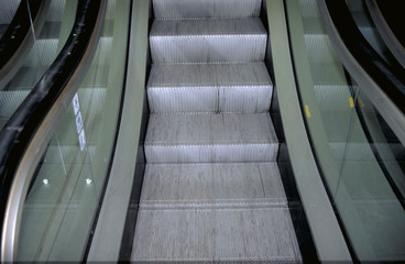 A picture taken from the bottom of an escalator that's going up.