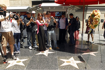 People pause to take photos and videos of the Bee Gees Walk of Fame star, where a wreath in memory of Robin Gibb has been placed, in Hollywood