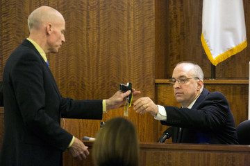 Prosecutor reviews a .22 caliber gun with State Police ballistics expert during the murder trial of former NFL player Aaron Hernandez in Fall River