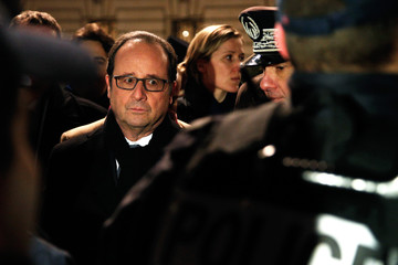 French President Francois Hollande smiles at a French policeman as he visits the security measures at the Champs Elysees Avenue in Paris