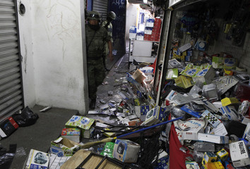 Soldiers stand next to electronic devices during an operation to seize fake brand-name products in downtown Monterrey