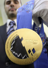 Employee holds a gold medal for the 2014 Winter Olympic Games during a presentation for the public at a jewellery shop in St. Petersburg