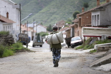 Local villager carries a sack at a village near Genting Ski Resort in Chongli county of Zhangjiakou