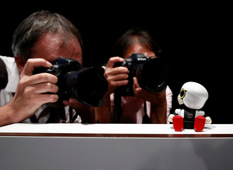 Photographers take picture of Toyota Motor Corp's Kirobo Mini robot during a photo opportunity after a news conference in Tokyo