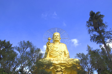 big golden buddha with blue sky and clouds.