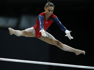 Larson of the U.S. competes on the uneven bars at the qualifying round of the Gymnastics World Championships at the Ahoy Arena in Rotterdam