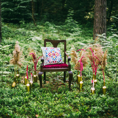 decorated wooden table served for two in the garden on grass on the riverbank. Boho and rustic style decoration with flowers, peacock feather, candles, clayware. Romantic date, table setting