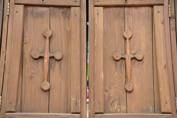 Wooden closed gates with crosses on the doors