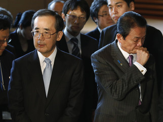Japan's Finance Minister Aso coughs while  Bank of Japan Governor Shirakawa answers reporter's question at their joint news conference in Tokyo