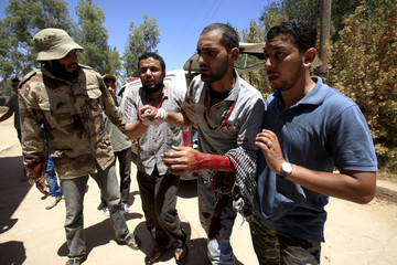 Libyan rebel fighters help their injured comrade at a field hospital near Misrata's western front line