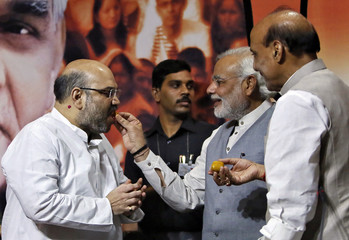 Indian PM Modi offers sweet to Shah, the newly appointed president of India's ruling BJP as outgoing BJP president Singh watches during a news conference in New Delhi
