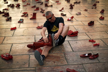 A man jokingly compares shoe sizes in an art installation of 745 pairs of female red shoes, put on display by Mexican visual artist Elina Chauvet to protest against gender violence and femicide, at La Constitucion Square in Malaga
