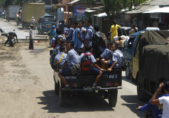 Student travel on a truck as as they return home from school in Subang