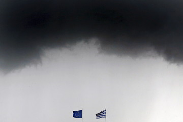 File photo of a Greek national flag and an EU flag fluttering under storm clouds in Athens