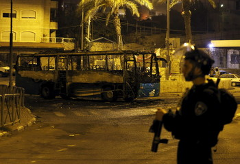 An Israeli border policeman stands near an Israeli bus that was attacked and set alight by Palestinian protesters in Arab east Jerusalem neighbourhood of Ras al-Amud