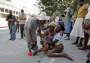 Haitian women react after their injured relative is carried away outside  a Cuban hospital in downtown Port-au-Prince