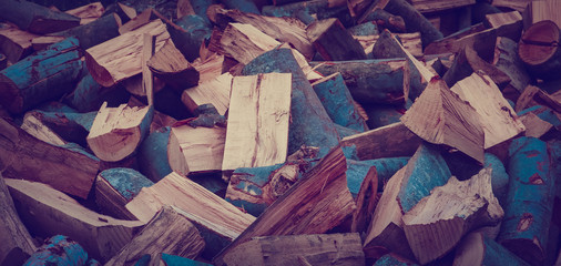 Chopped firewood on a stack, prepared for winter. Photo depicts a backdrop with birch firewood in a pile, hipster filter mood. Natural wooden background.
