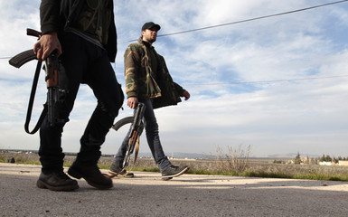 Free Syrian Army fighters walk as they seize Menagh military airport in north Aleppo