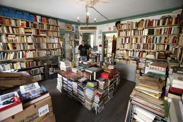 Nicolas Mahieu poses inside his bookstore in Goussainville-Vieux Pays, north of Paris
