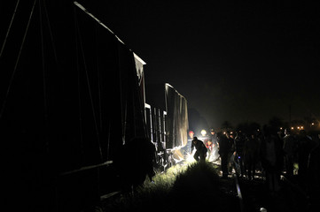 People inspect the wreckage of a military train crash in the Giza neighbourhood of Badrashin