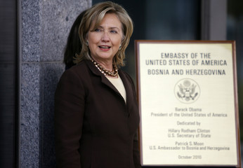 U.S. Secretary of State Hillary Clinton poses beside a plaque commemorating the opening of the new U.S. embassy in Sarajevo