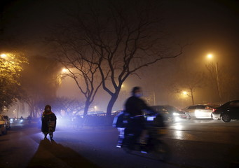 People wearing protective masks ride motorcycles in the night during a heavily polluted day in Beijing