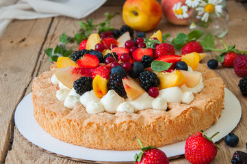 Homemade dacquoise cake with wipped cream cheese garnished with summer berries and peaches, close up.