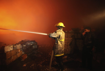 alestinians extinguish fire from a medicine storage facility in the northern Gaza Strip