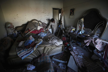 A resident salvages belongings in a room after a bomb blast, a day earlier, in a residential area in Karachi