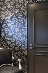 Resting corner with gray door with black wallpaper and golden flowers and gray armchair