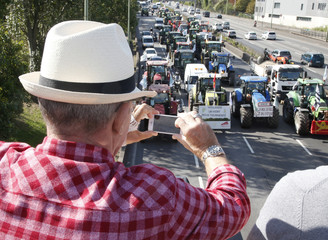 People standing on a bridge take pictures as French farmers converge on Paris, driving their tractors on the motorway