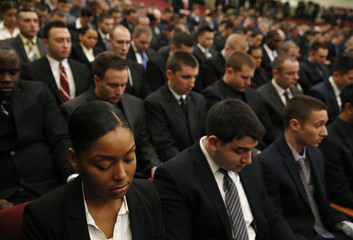 New recruits for the NYPD take a moment of silence for those killed and injured in the militant attack in France during a swearing-in ceremony for new recruits at Queens College in New York