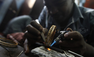 An employee makes a bangle at a jewellery work shop in Colombo