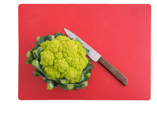Green cauliflower on red cutting board with knife.