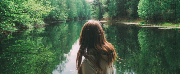 girl stands with his back to the camera. against the background of a beautiful river. green forest
