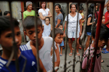 People gather outside a house where two men were killed during a drugs related police operation in Manila, Philippines