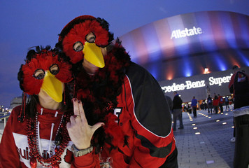 Louisville Cardinals fans wear mascot masks before the Cardinals play Florida Gators in their 2013 Allstate Sugar Bowl NCAA football game in New Orleans